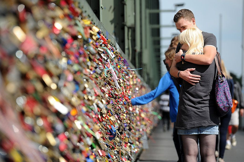 A couple embraces after affixing their lock to the bridge in Germany.  #love #locks #padlocks #bridge