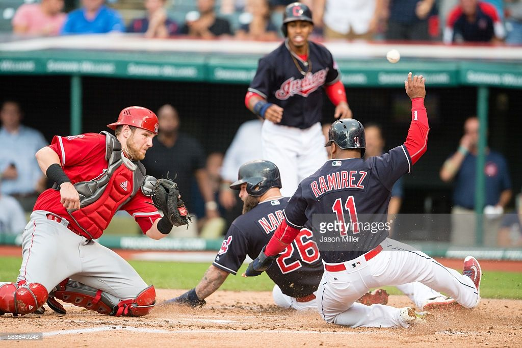 Catcher Jett Bandy #13 of the Los Angeles Angels of Anaheim misses the catch as Mike Napoli #26 and Jose Ramirez #11 of the Cleveland Indians score on a double by Lonnie Chisenhall #8 of the Cleveland Indians during the first inning at Progressive Field on August 11, 2016 in Cleveland, Ohio.