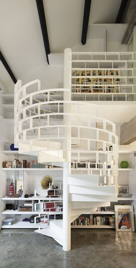 simple cut through white spiral stairs with the floor to ceiling bookshelf...classic!