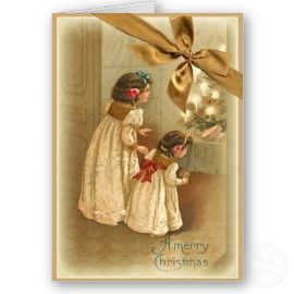 A Merry Christmas.  Two little girls in long white dresses look at a table top Christmas tree decorated with lit candles.  Vintage Cards.