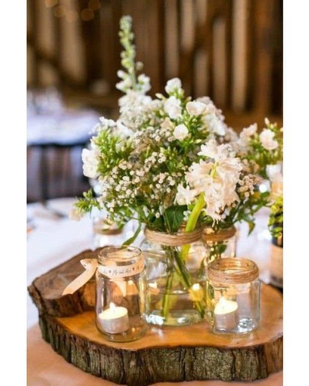 Centro de mesa floral con tarros de cristal velas y un for Como tratar un tronco de madera para decoracion