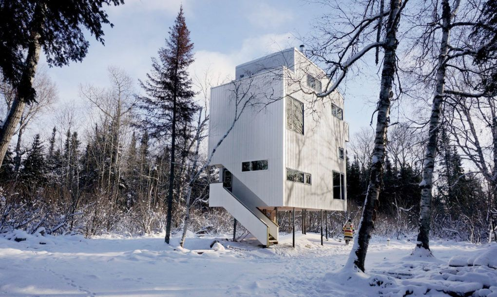 This year-round cottage on stilts in Canada floats above the site prone to floods and freeze-thaw weathering.