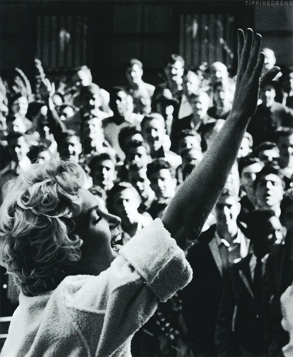 Marilyn Monroe happily waves to her adoring fans from her NY apartment during the filming of The Seven Year Itch, 1954.