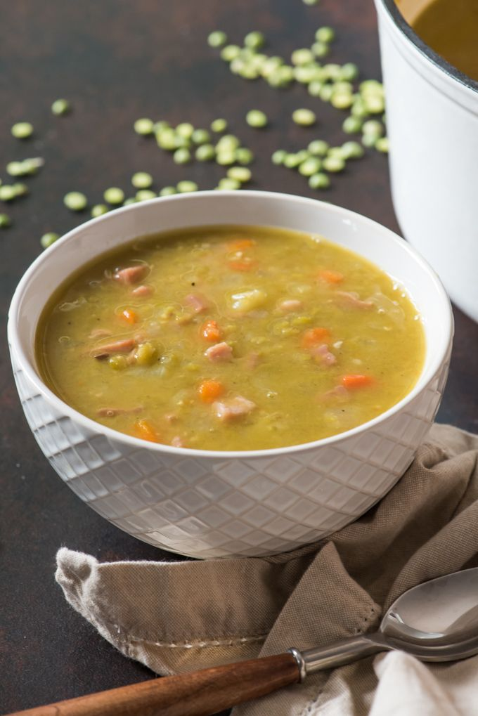 A white bowl of classic split pea soup made with ham and ...