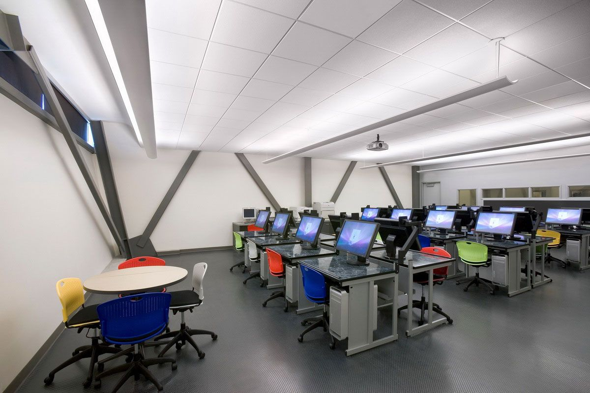 Amazing Computer Room Interior Design Of School Lab With Desk In Grey Color Matched Colorful Swivel Chairs Also Round Shaped White