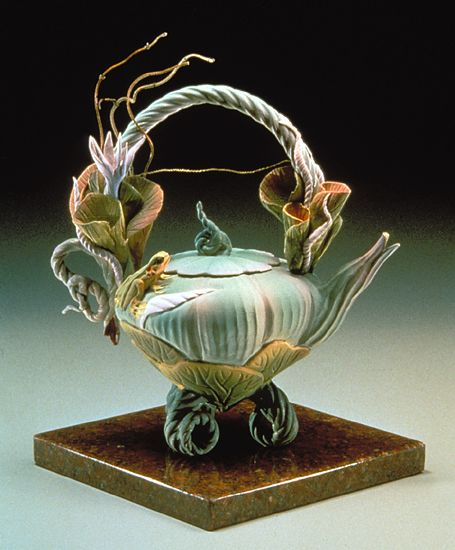 """""""Jade Lily Tea""""  Ceramic Teapot    Created by Nancy Y. Adams  Wheel thrown and hand-built earthenware teapot with a hand-carved water lily motif and a hand-modeled frog. Decorated with airbrushed glazes. Signed on bottom. Non-functional."""