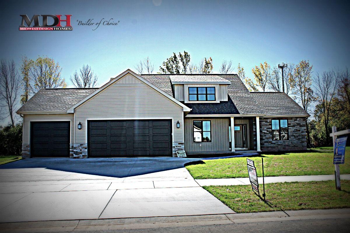 Modern exterior in clay siding with black windows, black garage ...