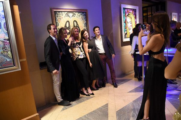 Guests pose for a photo at the Underwater Dreams To Life In Color - Art Exhibit Featuring Antonio Dominguez De Haro And Romero Britto At Four Seasons Hotel Miami at The Four Seasons Hotel on December 3, 2016 in Miami, Florida.