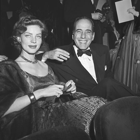 Lauren Bacall and Humphrey Bogart (1899 - 1957) smile while seated in formal evening wear at the Academy Awards, RKO Pantages Theater, Los Angeles, California. Bogart won for Best Actor in director John Huston's film, 'The African Queen.'