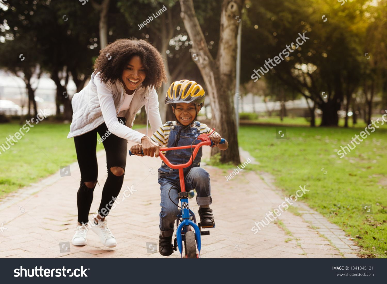 Happy Cute Boy Learn To Ride A Bike With His Mother Mother