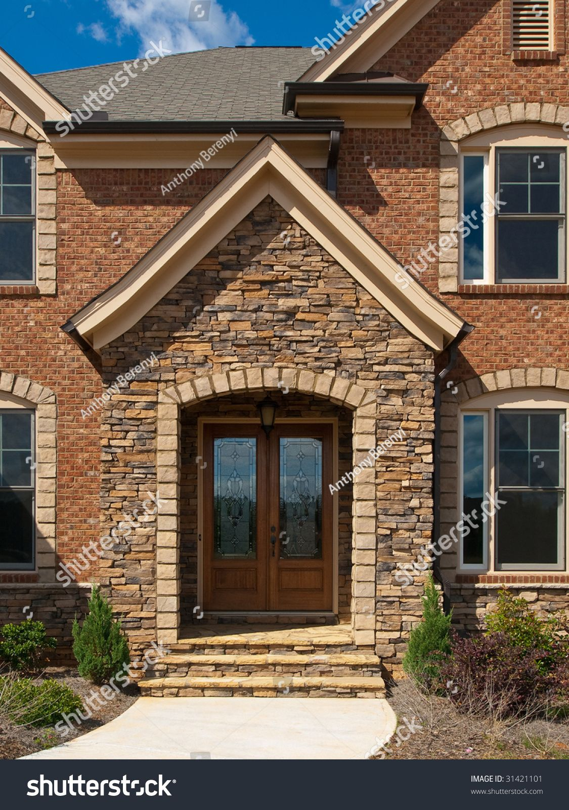Luxury Model Home Exterior stone arch front entrance view   stacked on limestone home exterior, paint home exterior, granite home exterior, painted stone home exterior, 2 story house exterior, faux stone home exterior, ledger stone home exterior, rock home exterior, stucco home exterior, cultured stone home exterior, natural stone home exterior, wood home exterior, stainless steel home exterior, acadian home exterior, brick home exterior, wainscoting home exterior, rock for house exterior, stacked stone home bar, concrete home exterior, shutters home exterior,