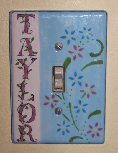 Hand painted light switch plate pottery for Taylor, using a flower stencil for the design.