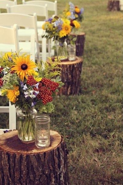 tree stumps with flower displays, great idea for a rustic wedding (Not sure what the other glass is for?!?)