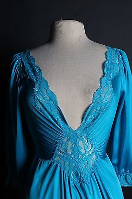This fantastic Vintage Olga nightgown is made of teal blue nylon and spandex and features 3/4 length sleeves, curve hugging bodice, intricate lace, and a huge sweeping skirt.  Olga Style number: 92470 Label size: Large Skirt length: 36 inches In wonderful condition, very supple and stretchy. #33