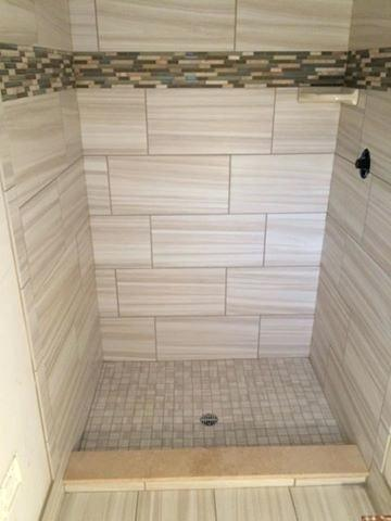 Custom Tiled Shower In 12x24 Porcelain Tile Installed At A 1 3 Staggered Vertically With A Glass And Stone Glas Custom Tile Shower Shower Tile Shower Wall Tile