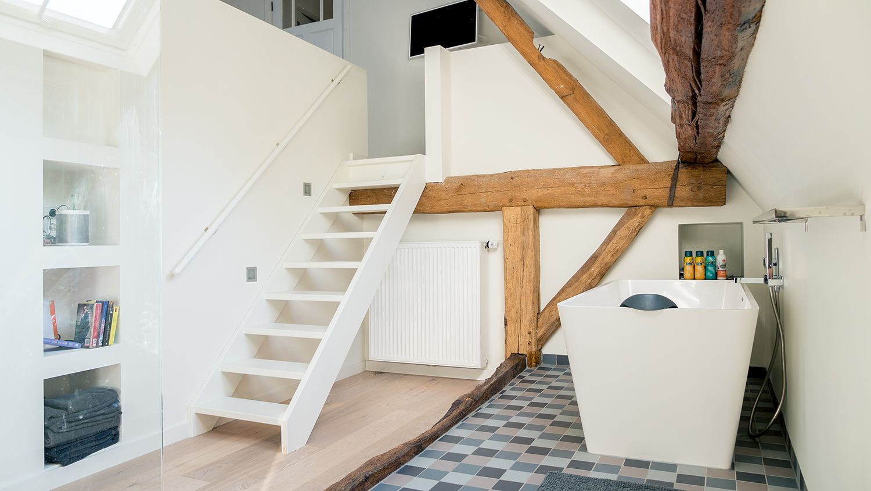 Open badkamer met ligbad en inloopdouche en trap naar slaapkamer ...