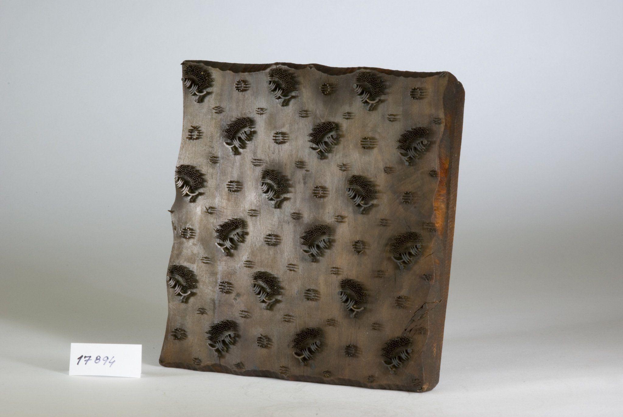 Forma modrotisková i.č. 17894 na ruční tisk se stylizovaný rostlin. vzorem z mosazných hrotů a plíšků. Pochází z barvířské dílny J. Ježíška z Val. Meziříčí z konce 19. stol. 24 x 23,7 x 5,1 cm