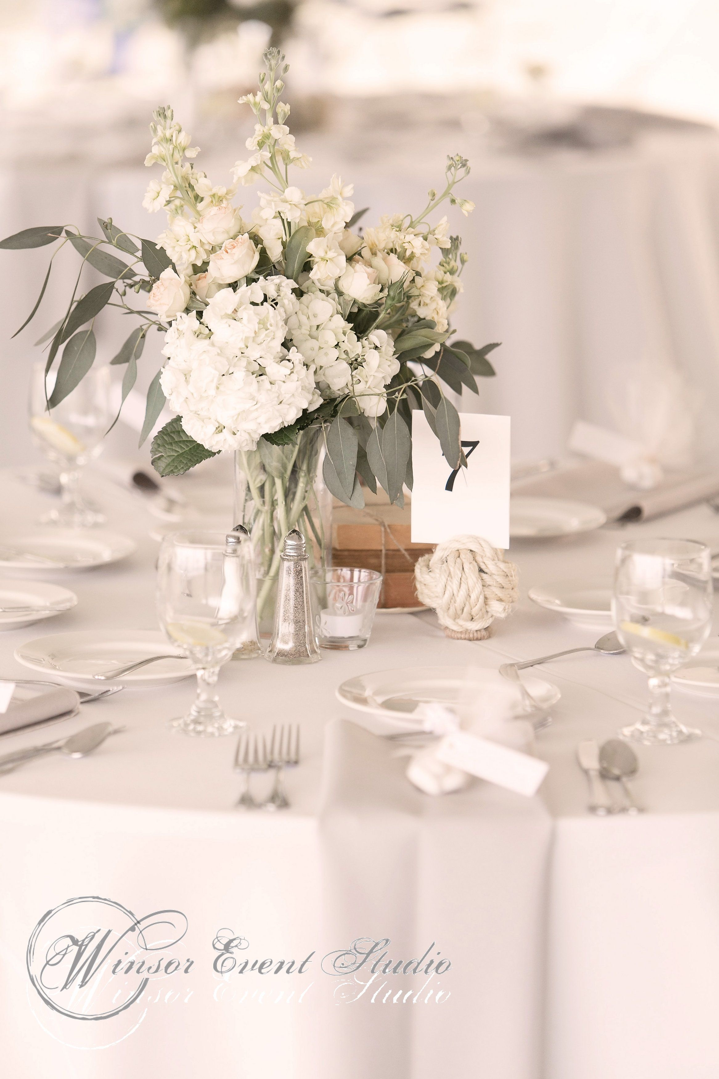 Centerpieces Of Hydrangea Seeded Eucalyptus Spray Roses And Creamy Stock In Vases Paired With
