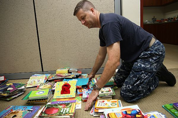 Lt. Cmdr. Glen D. Kitzman, chaplain, Military Sealift Command Far East, assists in dividing and categorizing the children's books that were donated during a book drive .