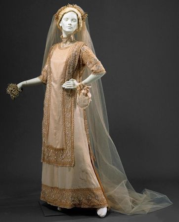 Cream silk taffeta wedding dress with embroidered tulle overlay, matching headdress and veil, Portuguese, 1912. Worn by the donor's mother, Maria da Madre de Deus Naples Souza Pacheco on her wedding day in 1912.
