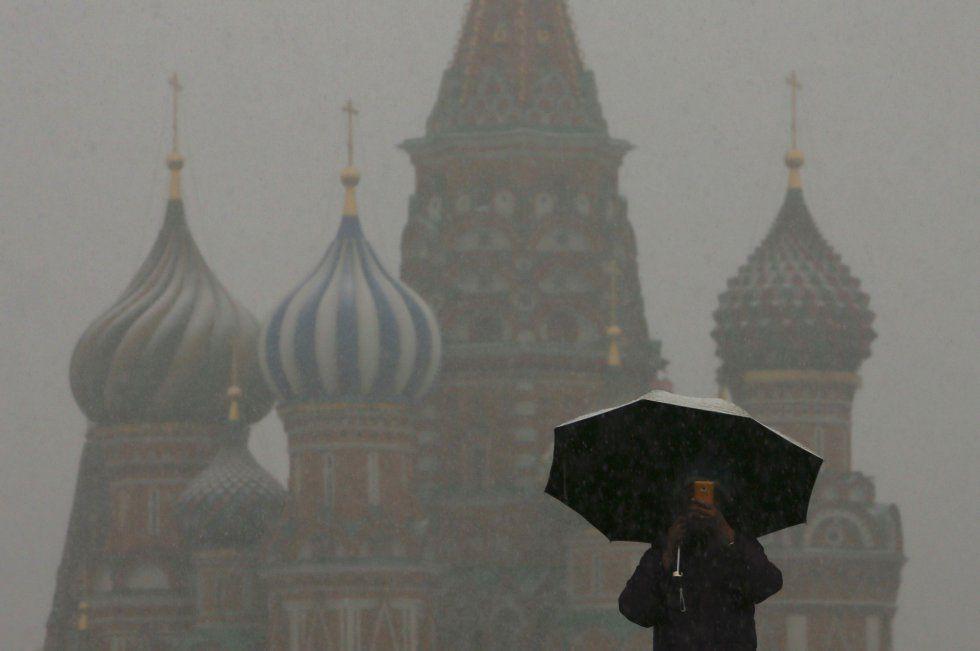 Un hombre camina con su paraguas durante una nevada en la plaza Roja de Moscú (Rusia). MAXIM SHEMETOV (Reuters).