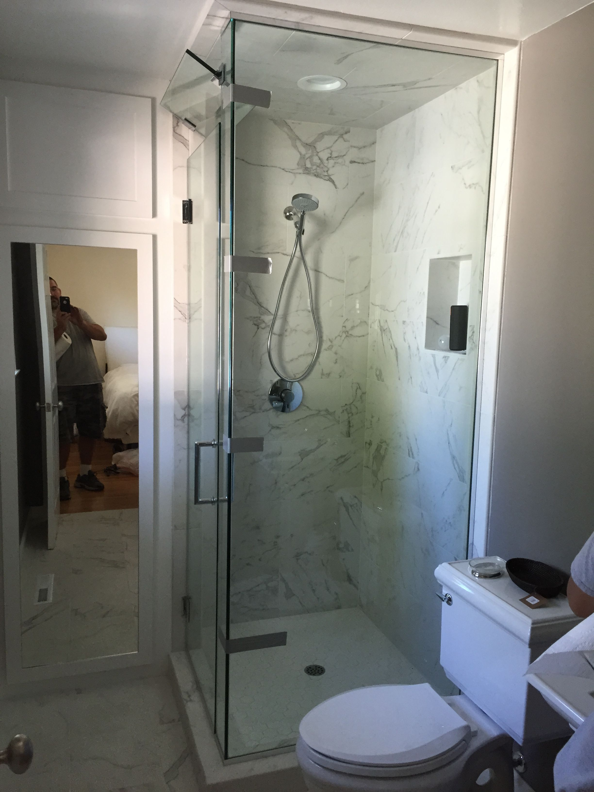 This frameless floor to ceiling glass shower enclosure has a glass transom above the door that opens to vent steam when bathing.  Installed in Santa Rosa, CA.