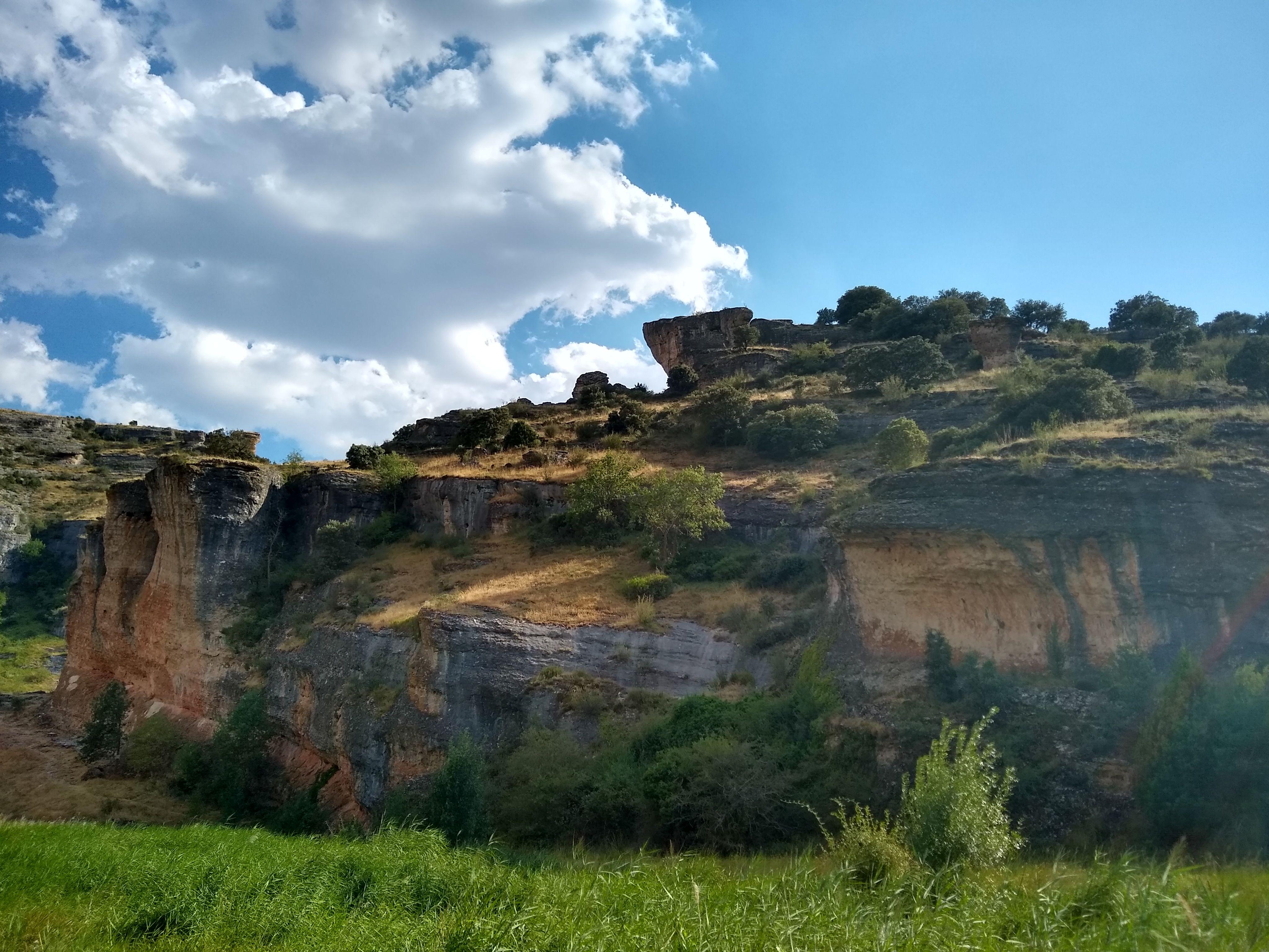 Vemos ante nosotros una pared de roca caliza de tonos anaranjados con coladas de tonos oscuros producidos por arrastre de materiales por la lluvia