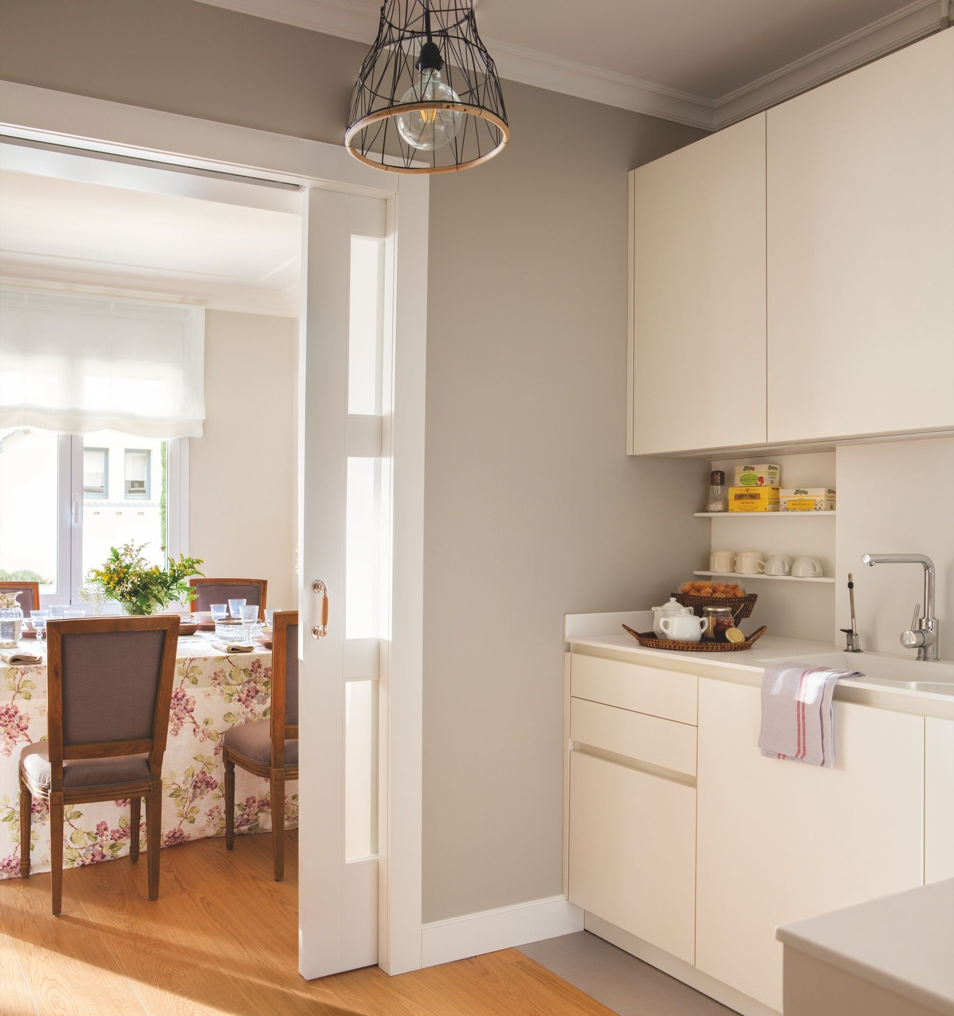 cocina con muebles blancos paredes grises y puerta