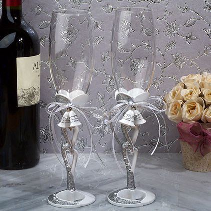 """Make a statement by raising these beautiful Wedding Bells Toasting Flutes at your reception! Crafted from a sturdy poly resin, these flutes feature an entwined hearts design, accented with wedding bell charms and shimmering silver glitter. Each set measures about 10"""" tall and comes packaged in a display gift box."""