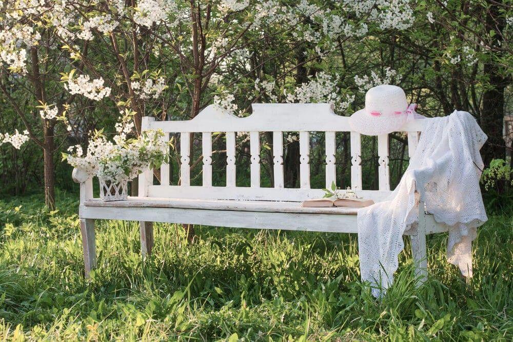Eine einfache weiße Gartenbank eingebettet auf dicken Gräser mit ...