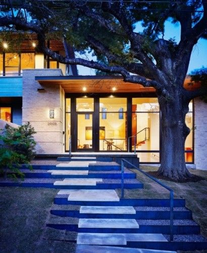 Artfully composed stone steps, lighted wooden eaves over extensive fenestration, and a majestic Live Oak. Hugh Jefferson Randolph Architects. Austin, TX.