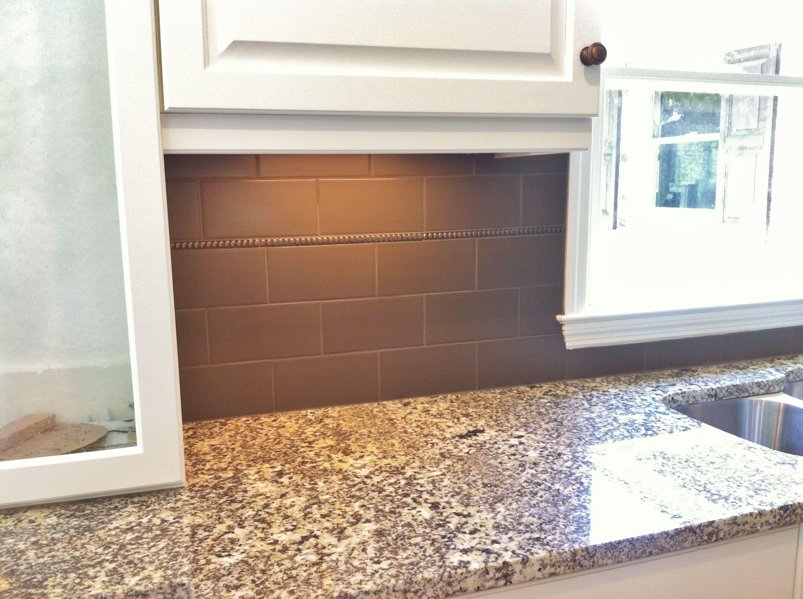 - 4x8 Porcelain Tile With Bronze Accent At Kitchen Backsplash
