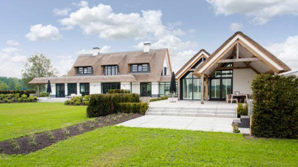 Witte villa rieten dak stucwerk gevel zwarte kozijnen natuursteen