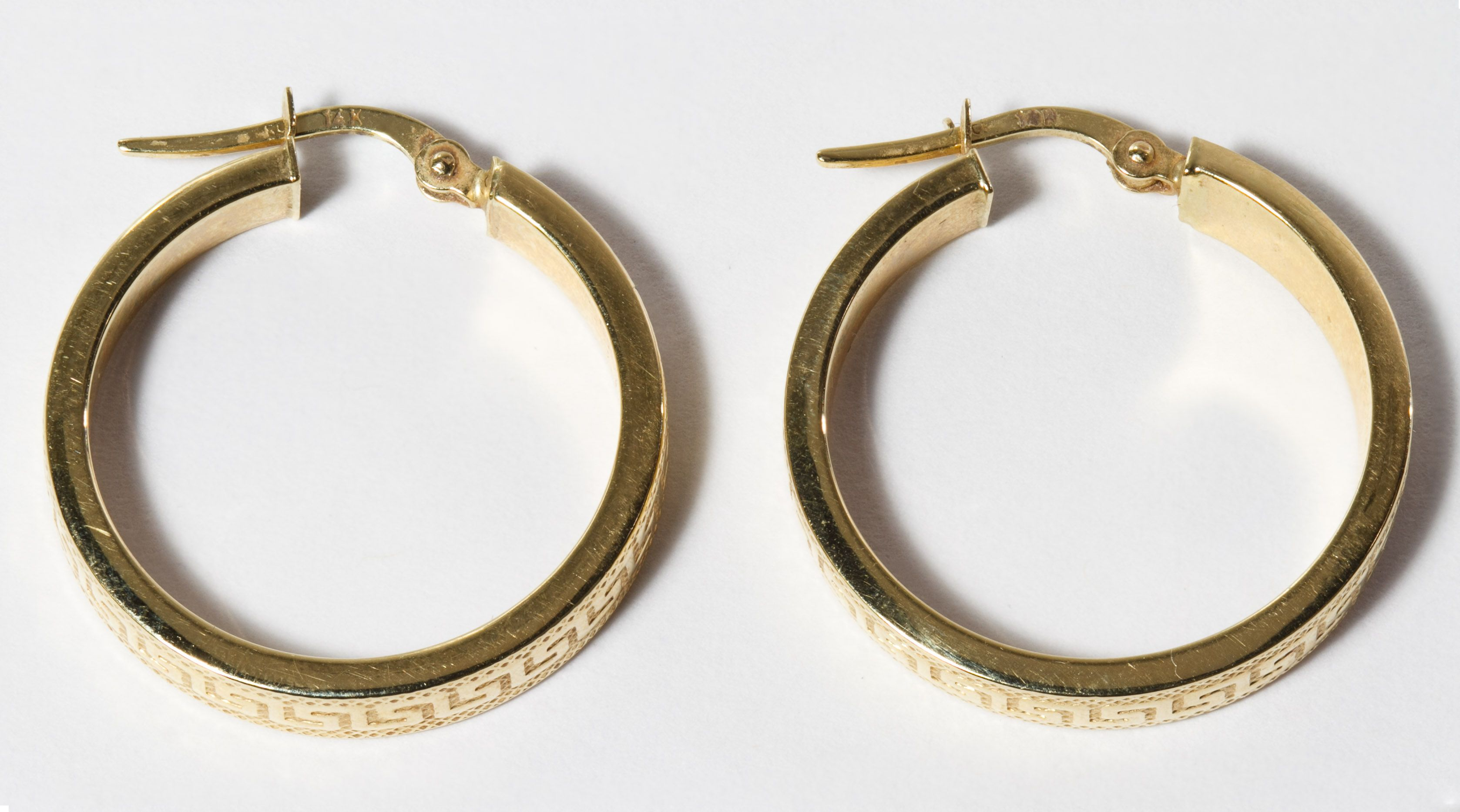Lot 142: 14k Gold Pierced Hoop Earrings; Having a Greek key design on outside of hoop; marked on posts