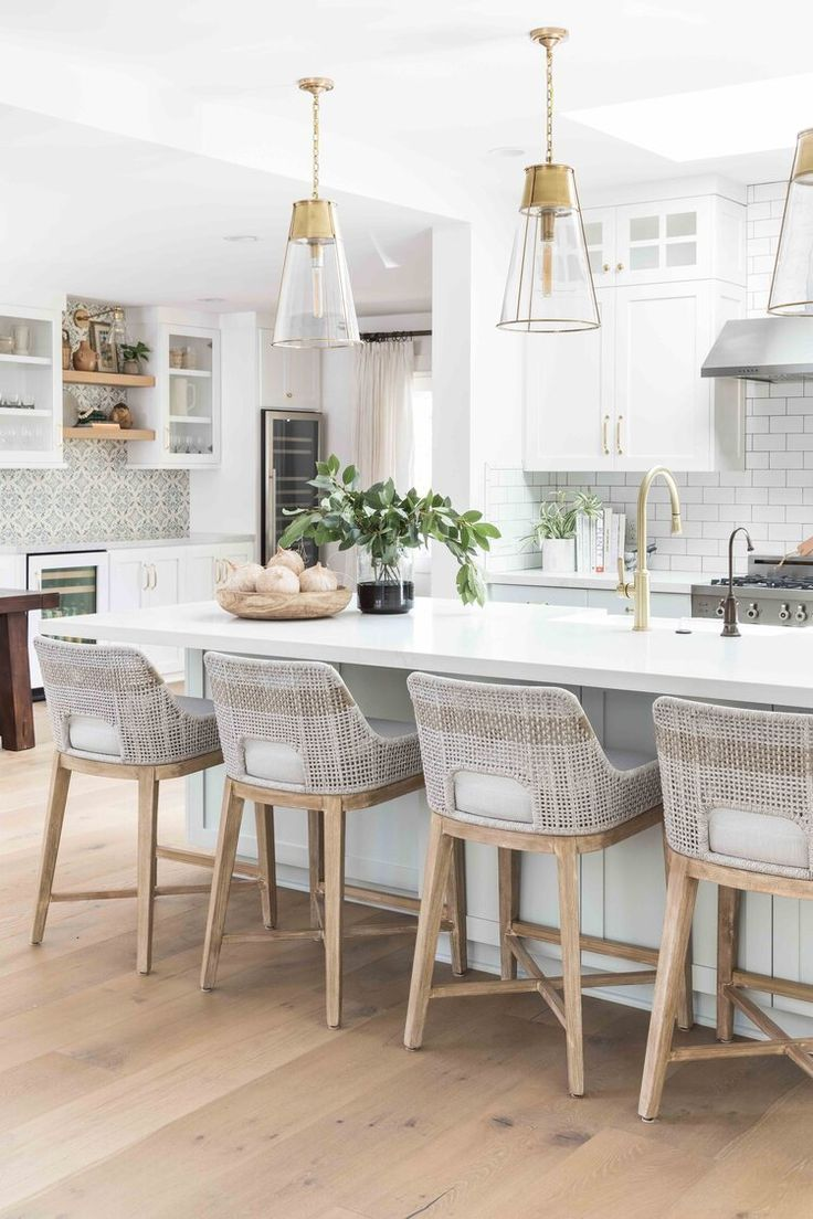 Love everything about this bright white kitchen.  The counter stools are perfect with the wood base and the brass and glass pendants balance out the space #whitekitchen #kitchendesign