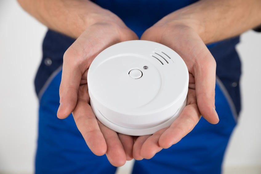 photo of person holding a smoke alarm