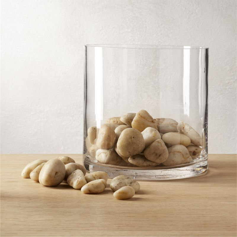 Shop natural river stones.   Invite the outdoors in with a bed of natural stones.  Unique in size and color, the soft tone and organic shape lend a sense of zen to centerpiece bowls and decorative vases.