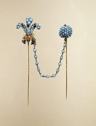 Double cravat pins. This pair of cravat pins are made of gold. One pin has a three Prince of Wales feathers' design in torquoise and enamel which is linked by a detachable torquoise-set chain to the companion pin headed in a raspberry design.