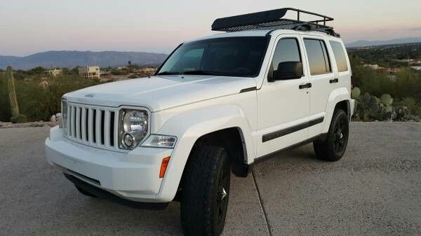 Lifted White Jeep Liberty With Rockstar Rims And Roof Rack