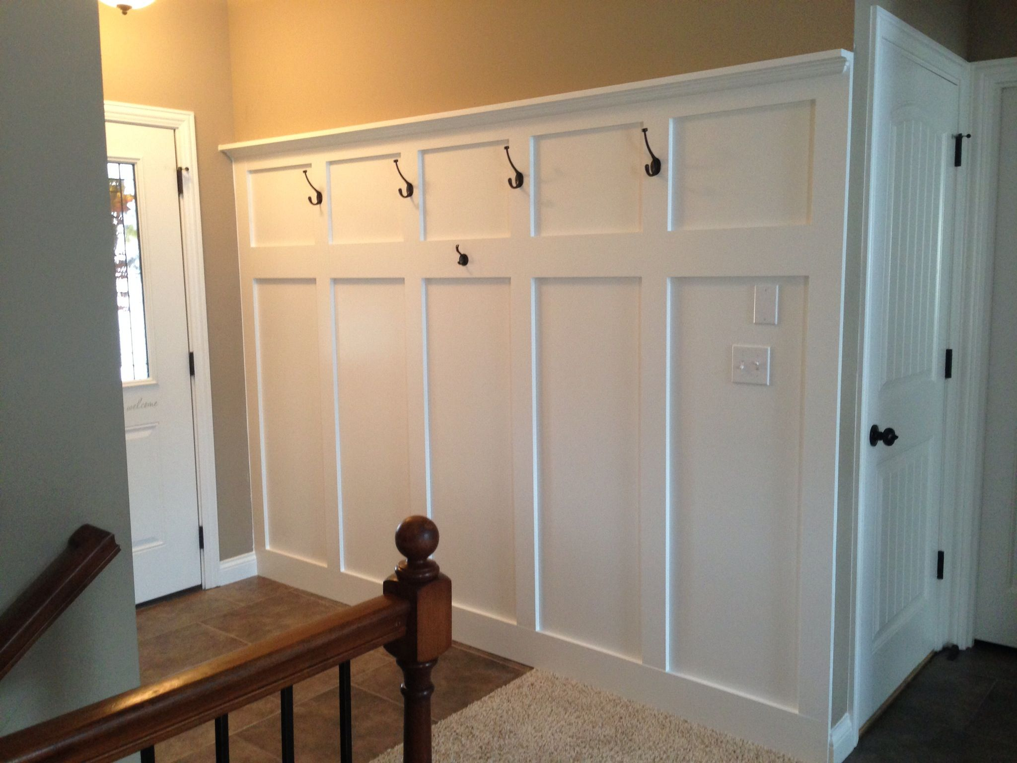 Entryway wainscoting with hooks for coats and a shelf for ...