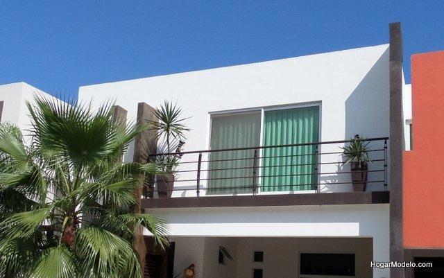 Fotografía de casa con balcón y baranda metálica en un diseño limpio