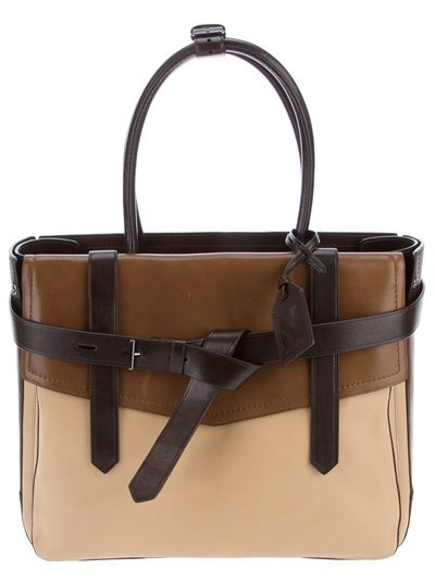 Brown leather bag from Reed Krakoff featuring two rolled top handles fastened with a buckled belt, a luggage tag, a tricolour panelled design, a front flap, a weaved belt to the top with a silver-tone buckle, an embossed logo to the back, a dark satin lining, an internal zipped pocket and a metallic logo plaque.