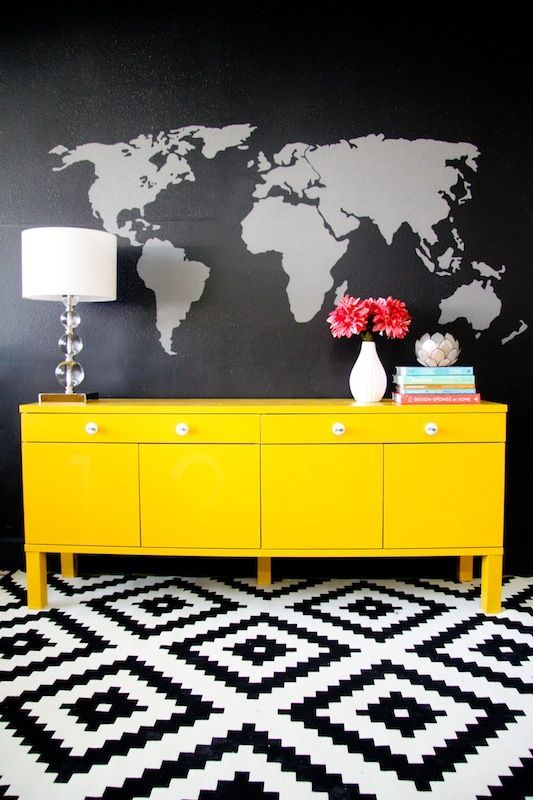 Sort of love this black wall with white world map on it! Paired with bright furniture, hmmm.