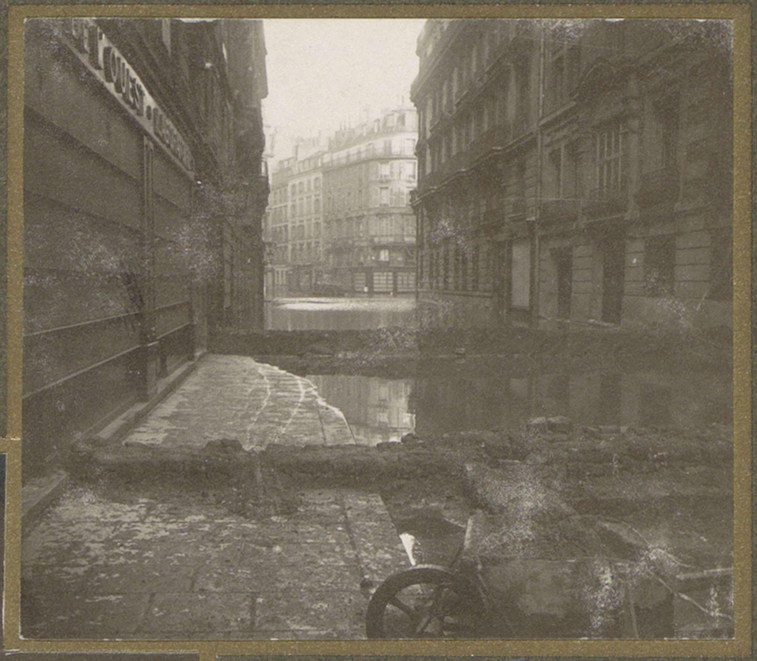 G. Dangereux | Ondergelopen straat met dammen en een kruiwagen, G. Dangereux, 1910 | Onderdeel van fotoalbum overstroming Parijs en voorsteden 1910.