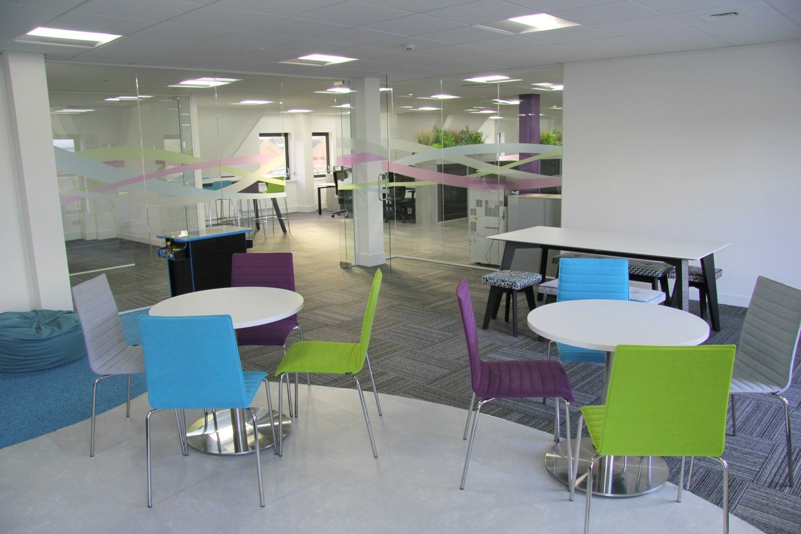 Workplace breakout area with blue and lime chairs furnished