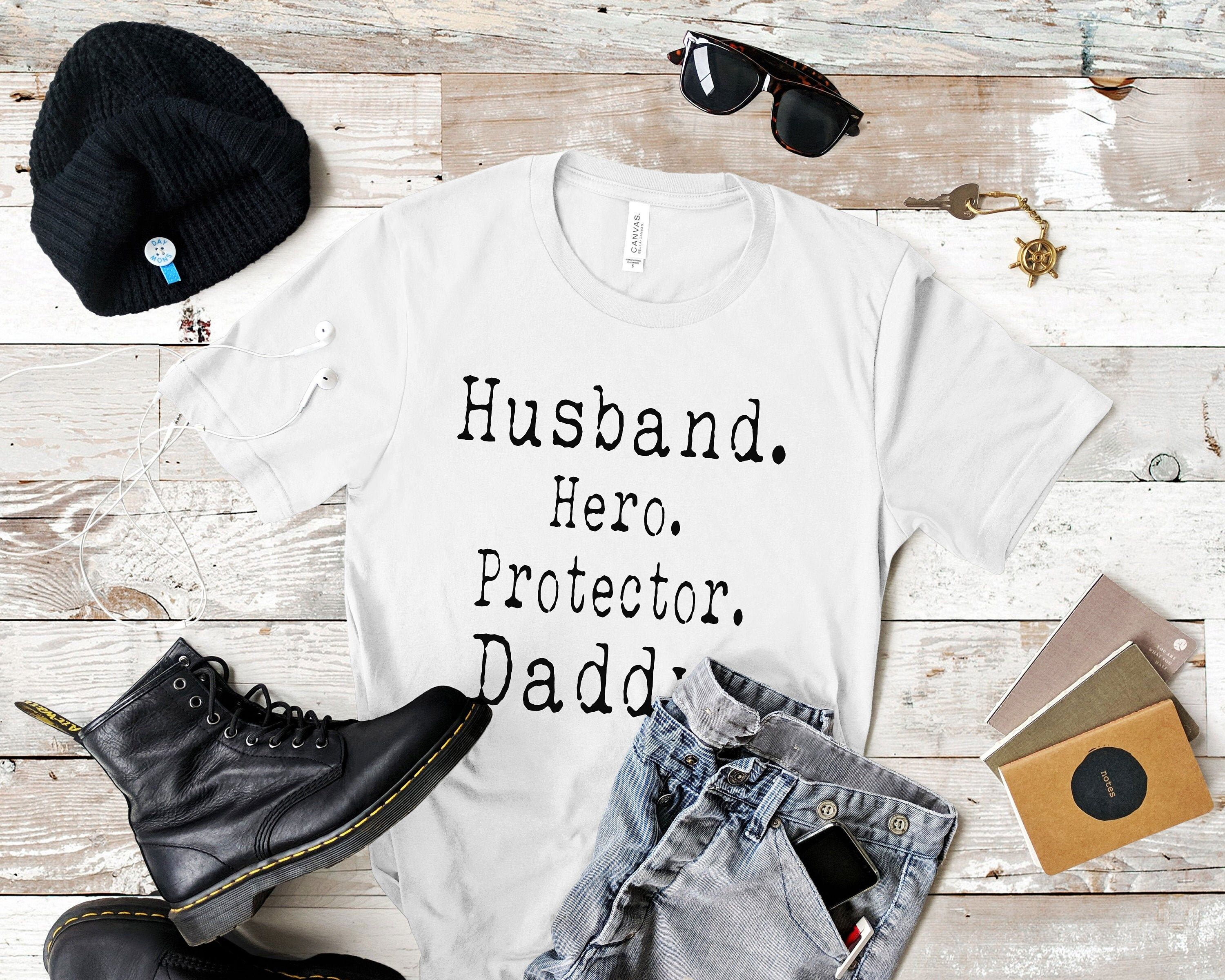 Husband, Protector, Hero & Daddy T-Shirt by ChubbyRhino Fathers are more than just Dad's, they're Husbands's, Protector's and most importantly Hero's! Tell him how much he means to you with this perfect Fathers Day Gift T- shirt. We only use the highest quality tees for all of our designs, we want you to feel as good as you look! They're super soft and incredibly comfortable which is why we have invested in only the best products. These tees are super versatile... you can roll up your sleeve