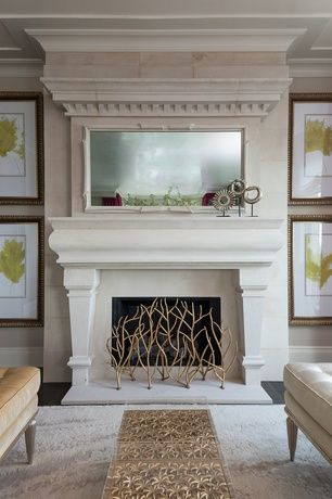living room with brass and glass coffee table aged gold sculptures white stone fireplace mantel