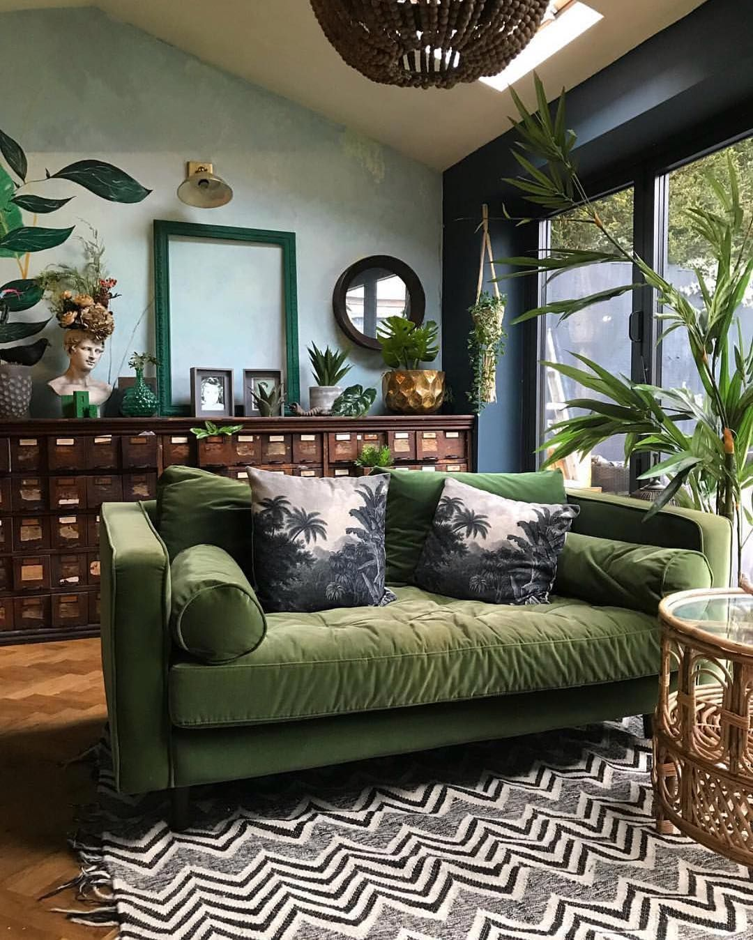 Green sofa and accents plants and vintage library chest in this eclectic living room