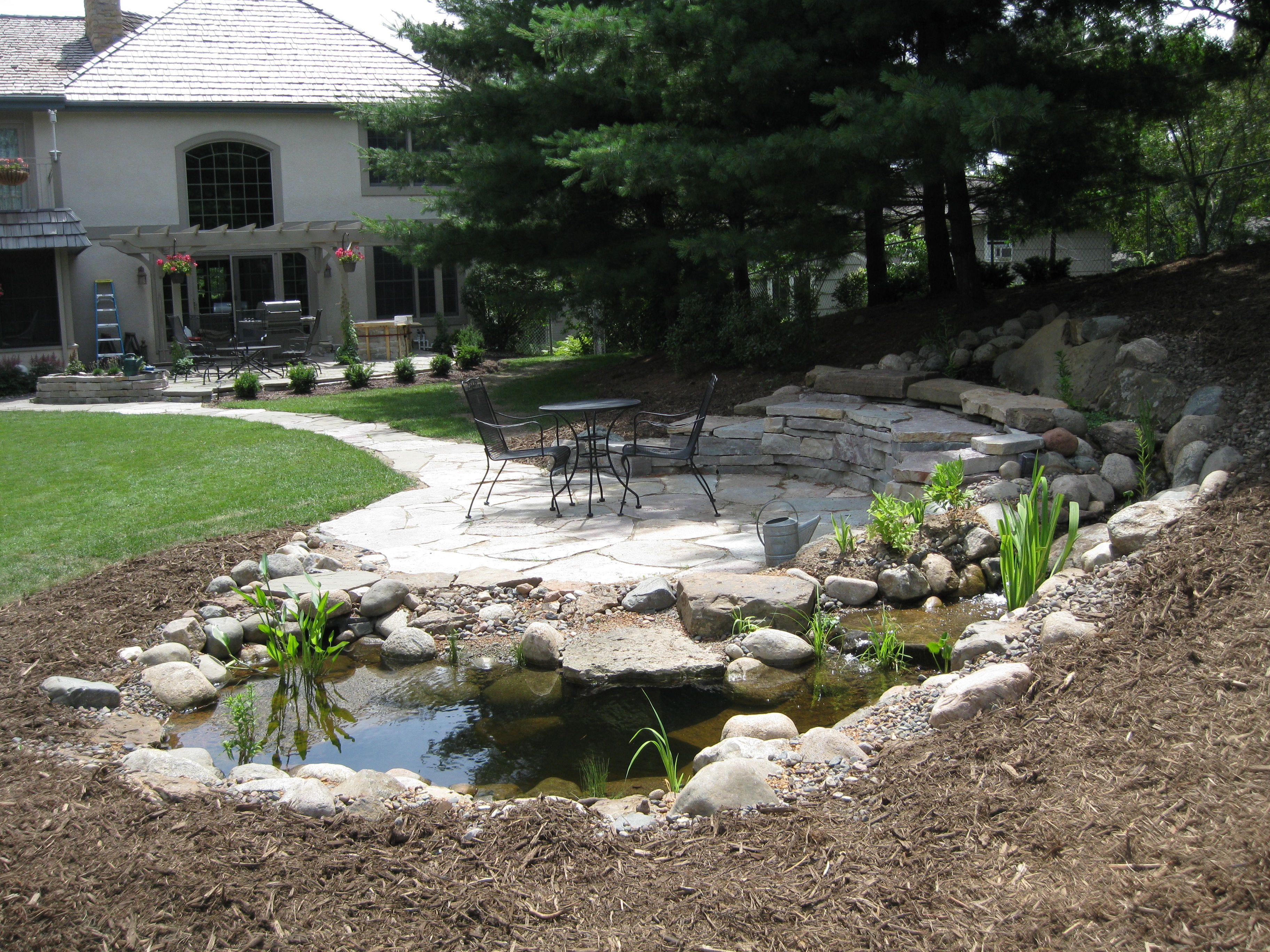 backyard terrace with stone sitting and a water element