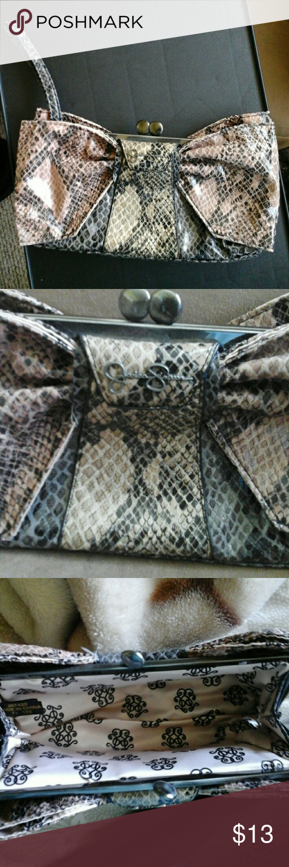 Jessica Simpson Clutch Tri-color snake skin print Jessica Simpson Clutch with wrist strap and snap closure. The bows for back and front are beige/pink,where it says Jessica Simpson is dark yellow and the base is greyish black. Very cute and roomy. Only used once. It's 8 inches long, 4 inches tall and width is about 2 to 3 inches. Jessica Simpson Bags Clutches & Wristlets